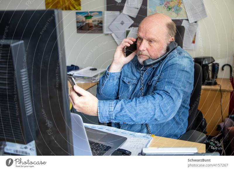 Mann sitzt vor PC, telefoniert mit 2 Geräten gleichzeitig und checkt auf weiterem Smartphone Nachrichten. Telefon Telefongespräch SMS Büro Kommunikation
