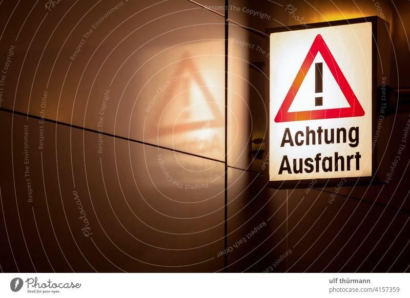 Achtung Ausfahrt Hinweisschild Verkehrsschild nachts beleuchtet Warnschild Zeichen Sicherheit Außenaufnahme Warnhinweis Vorsicht Gefahr Schutz