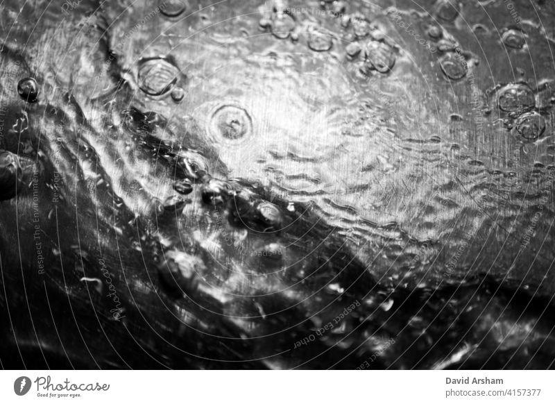 Kontrastreiches Wasserplätschern mit Blasen auf Metall fließen Oberfläche Durst vertreiben graphisch Rippeln abstrakt Stimmung Hintergrund erfrischend rein