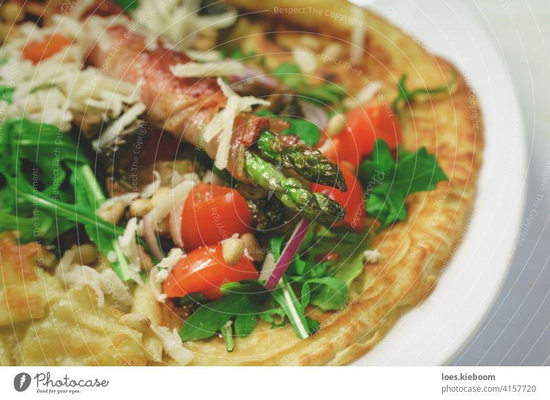Mediterranes Gericht aus Pfannkuchen mit gebratenem Spargel, umwickelt mit Speck, garniert mit Rucola, Parmesan, Tomaten und Pinienkernen Prosciutto mediterran