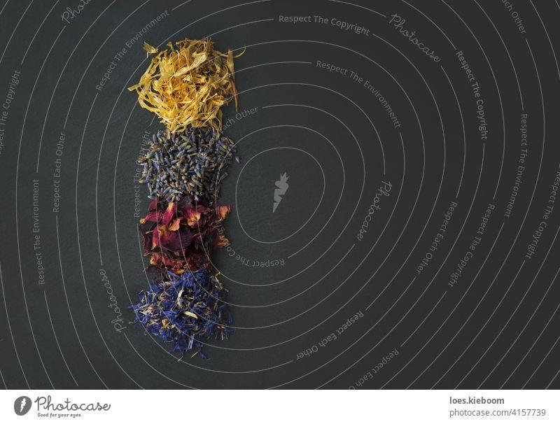 Draufsicht auf Blütenkräuter - getrocknete Ringelblumen-, Lavendel-, Rosen- und Kornblumenblütenblätter als Zutaten zum Kochen Küchenkräuter Roséwein natürlich