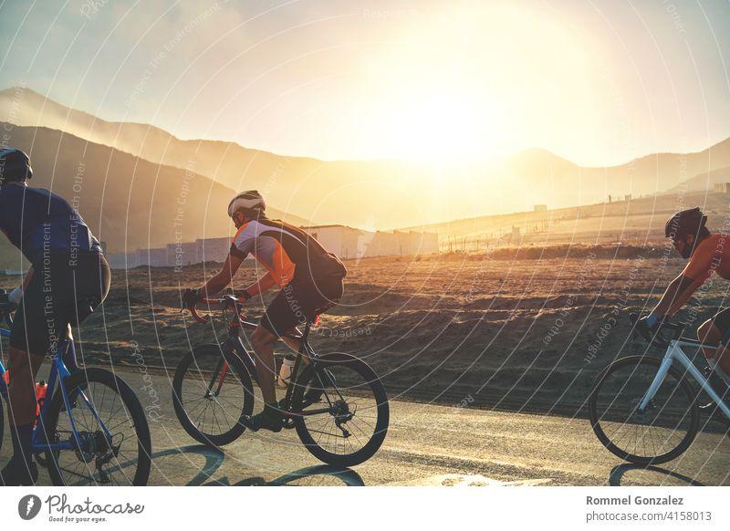 Gruppe von Radfahrern Freunde Reiten Rennen Fahrrad auf Sonnenuntergang Autobahn, Sonnenuntergang Fahrrad Wettbewerb. Menschengruppe Fahrradfahren professionell