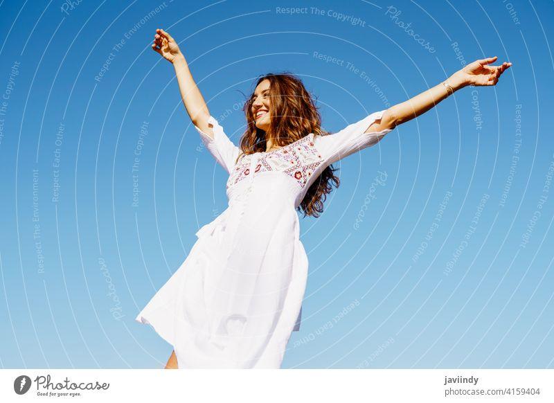 Junge Frau hebt ihre Arme in einem schönen weißen Kleid gegen einen blauen Himmel Mode Mädchen winken offen Waffen Behaarung copyspace Erweiterungen Frisur