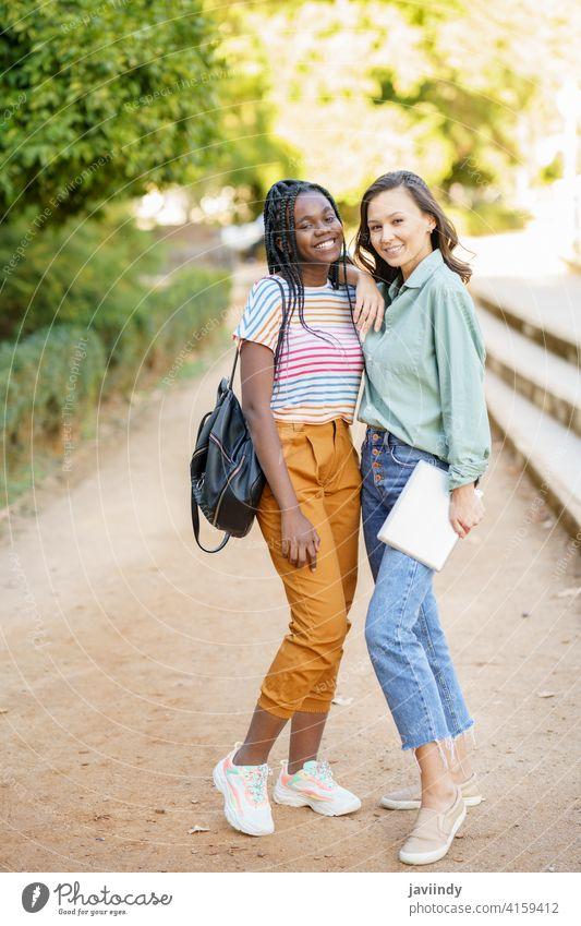 Zwei multiethnische Frauen posieren zusammen mit farbenfroher Freizeitkleidung Freund Tablette digital Mädchen jung Lifestyle urban schön Gerät außerhalb lässig