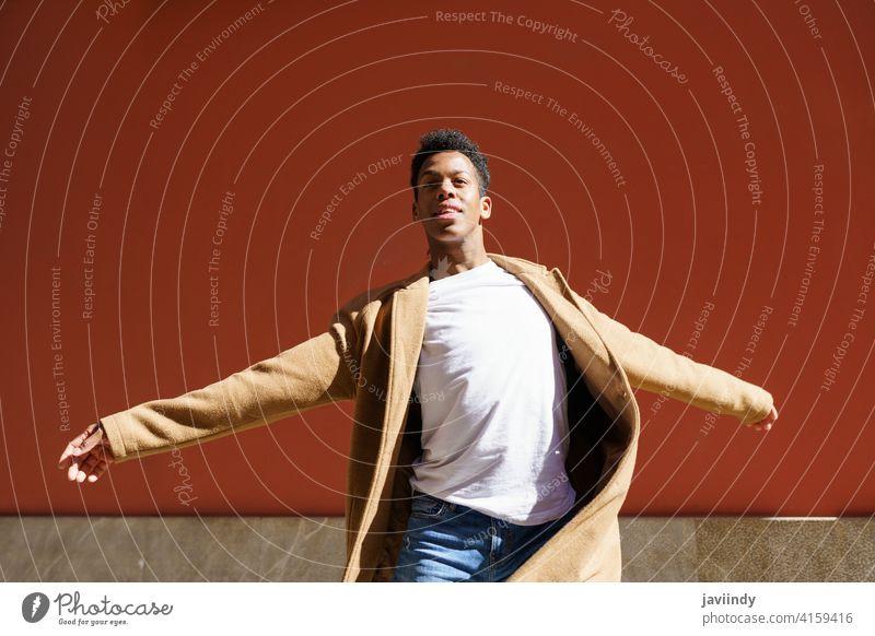 Junger kubanischer Mann tanzt auf roter Stadtmauer. schwarz Tanzen Straße Fröhlichkeit männlich Kubaner jung Ausdruck Person Glück Blick Tänzer im Freien eine