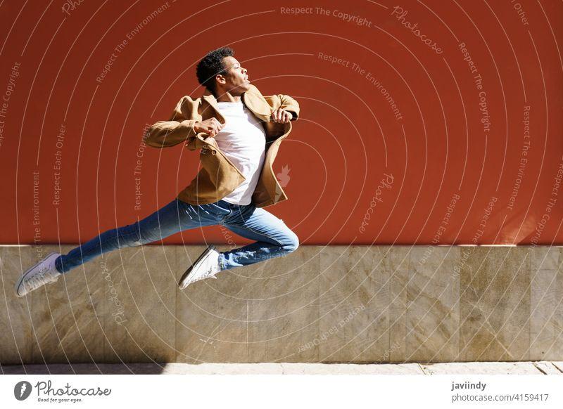 Junger schwarzer Mann macht einen akrobatischen Sprung mitten auf der Straße. springen springend Fröhlichkeit männlich Kubaner jung Person Glück Tänzer