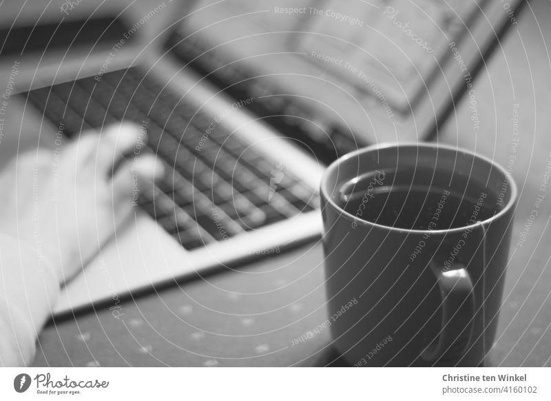 Hand einer Frau, die zu Hause am Notebook arbeitet. Im Vordergrund ein Becher mit Tee. Homeoffice Homeschooling Online-Vorlesung Laptop Computer junge Frau