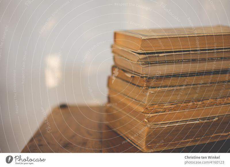 Ein Stapel alter, vergilbter und zerlesener Bücher liegt auf einem kleinen Holztisch vor einer hellen Wand mit Sonnenreflexen. Welttag des Buches am 23. April.