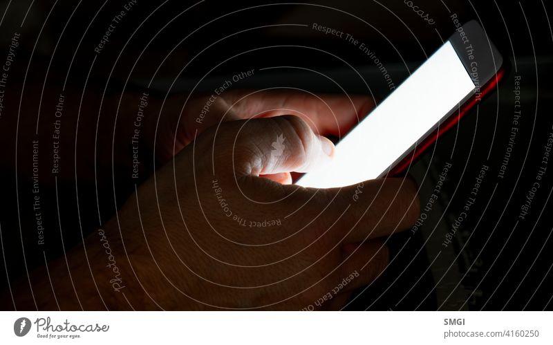 Nahaufnahme der Hände eines Mannes bei Nacht, der das Smartphone benutzt. Schlafstörung Person Bett Schlafzimmer heimwärts Telefon Internet dunkel Sucht