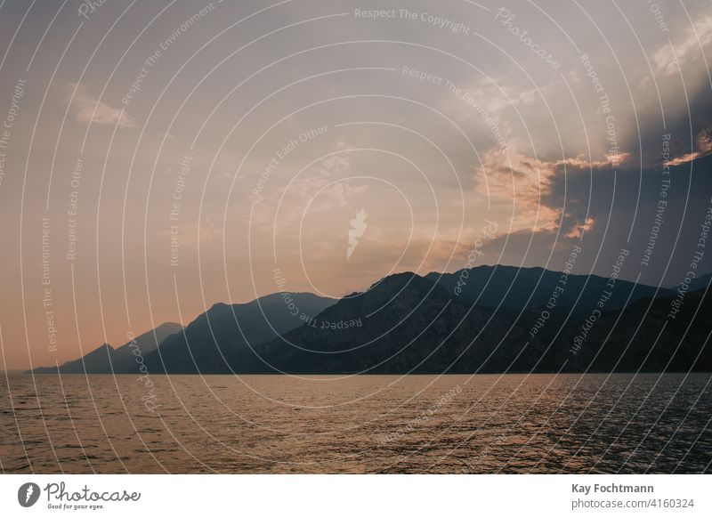 Sonnenuntergang gegen Bergkette Alpen schön Schönheit Boot Wolken Küste farbenfroh Ausflugsziel Europa Abend Freiheit Garda Hoffnung Horizont idyllisch