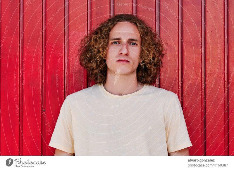 Porträt eines ernsten jungen Mannes mit lockigem Haar und grünen Augen, der in die Kamera schaut, mit rotem Hintergrund che attraktiv Person männlich Typ lässig