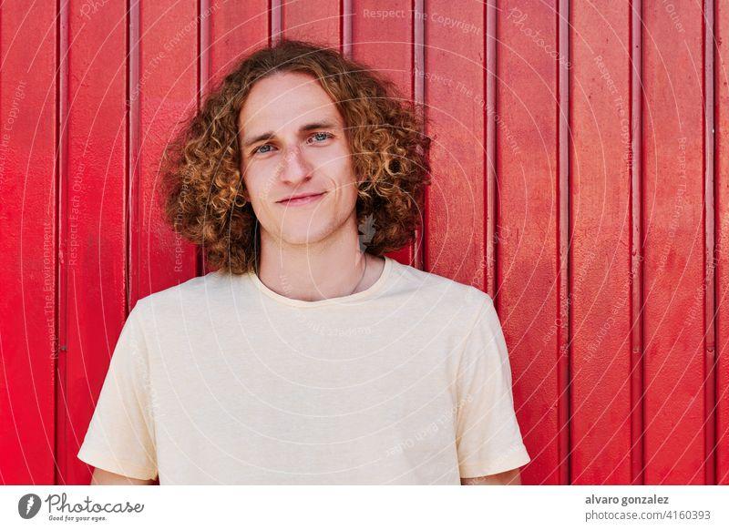ein junger Mann mit lockigem Haar und grünen Augen, der lächelnd in die Kamera schaut attraktiv Person männlich Typ lässig weiß gutaussehend eine vereinzelt