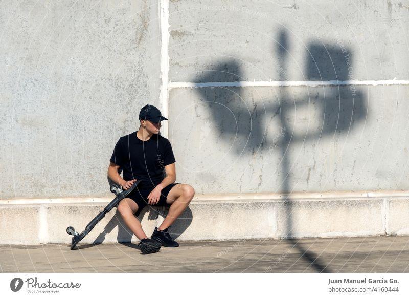 Schwarz gekleideter Teenager mit Mütze beim Skateboarden im Industriegebiet Parkplatz Verlassen abgestufter Haarschnitt solo Dachterrasse Ernsthaftigkeit