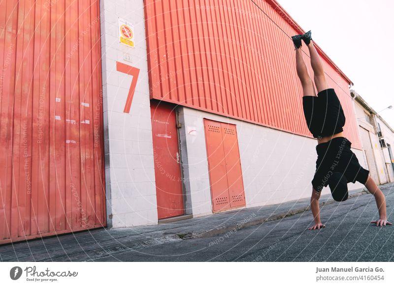 Junger Mann mit Kappe und schwarze Kleidung macht einen Handstand konfrontiert Industriegebäude mit der Nummer sieben Gleichgewicht Jugendlicher akrobatisch