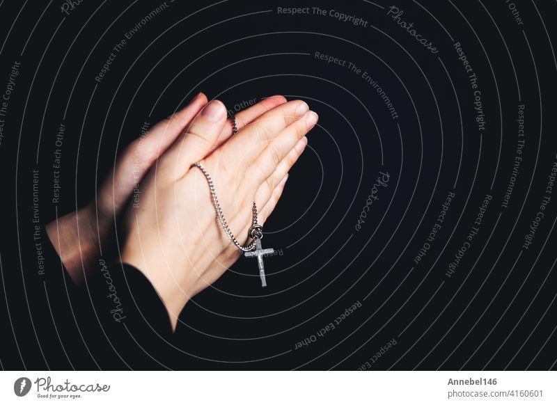 Betende Hände halten einen Rosenkranz, Closeup halten Halskette mit Kreuz, beten für Gott in der Dunkelheit, religiöse christliche Symbol Hintergrund Frau Hand