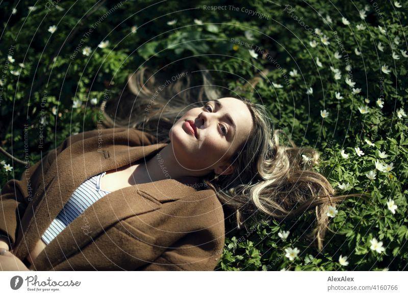 Ein blondes Mädchen liegt im Wald in einer blühenden Wiese auf der Lichtung mit kleinen weißen Blumen und schaut nach oben in die Kamera Landschaft Freude