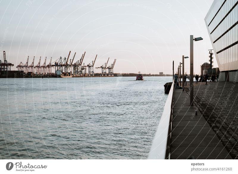 Hafenkräne, eine Fähre und Teile des Dockland Office Building Hamburg Hamburger Hafen pastell Wasser Elbe Fluss Deutschland Sonnenuntergang Außenaufnahme