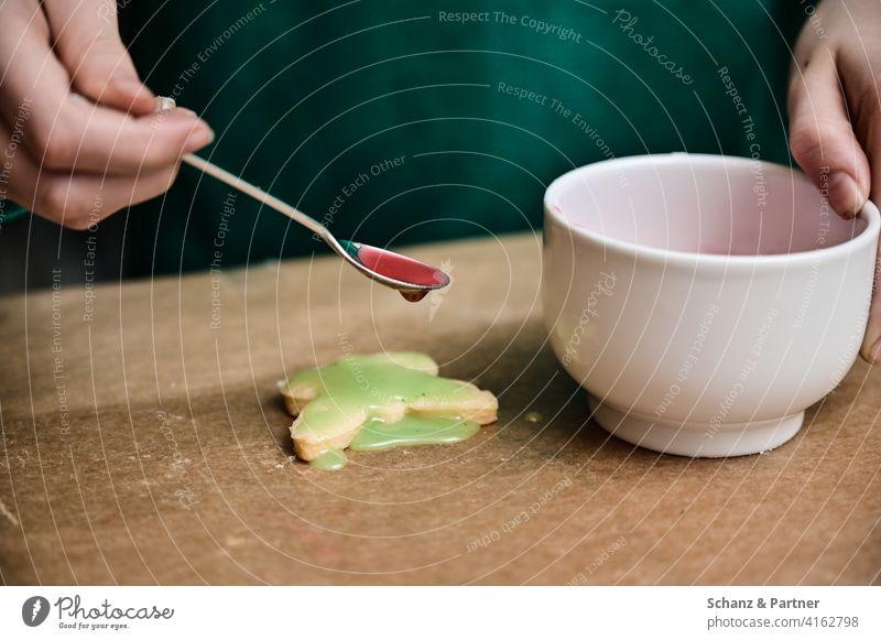 Kind tropft bunten Zuckerguss auf Weihnachtsplätzchen Plätzchen backen Weihnachten Löffel Schüssel Küche Backpapier Eltern Kinder Feiertage grün rot pink kekse