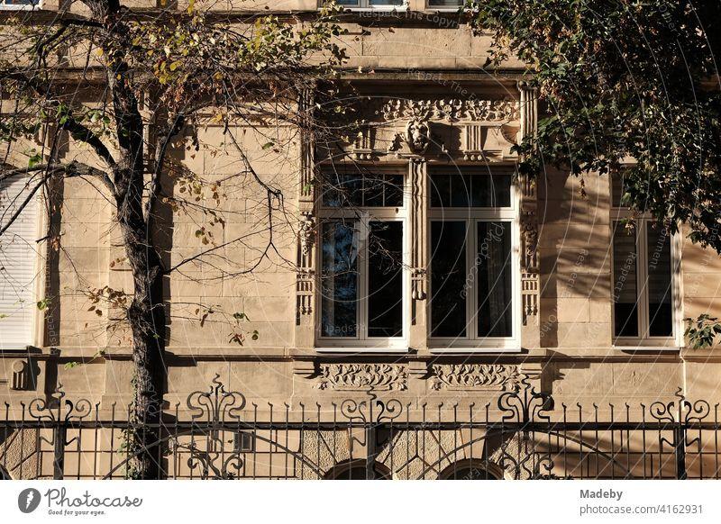 Prächtige und kunstvoll verzierte alte Villa aus hellem Sandstein im Sonnenschein im Westend von Frankfurt am Main in Hessen Altbau Fassade Fenster Verzierung