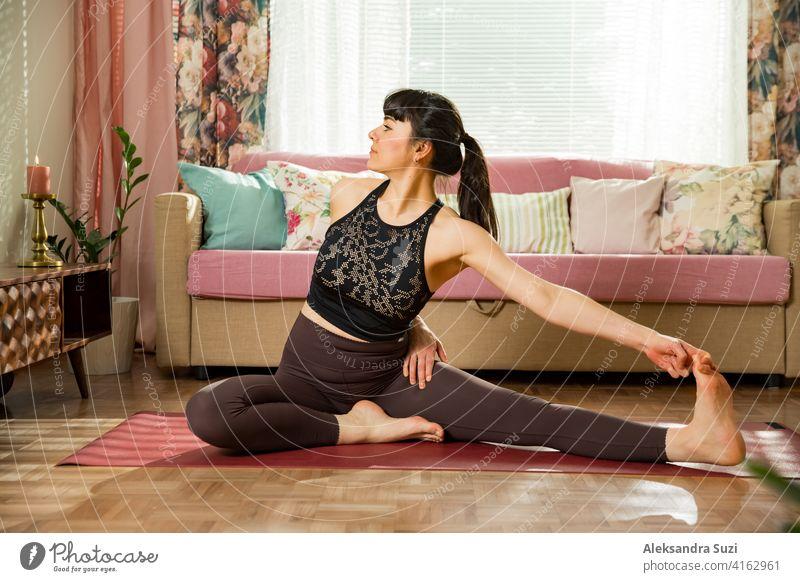 Junge schöne Frau übt Yoga zu Hause. Stilvolle gemütliches Zuhause Interieur. Doing Yoga-Übungen und genießen Sie den frühen Morgen. Gesunder Lebensstil aktiv