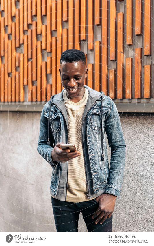 Porträt eines jungen afroamerikanischen Mannes Afroamerikaner Afrikanisch per Telefon Straße Tippen Handy Vorderansicht schauendes Telefon schwarz ethnisch
