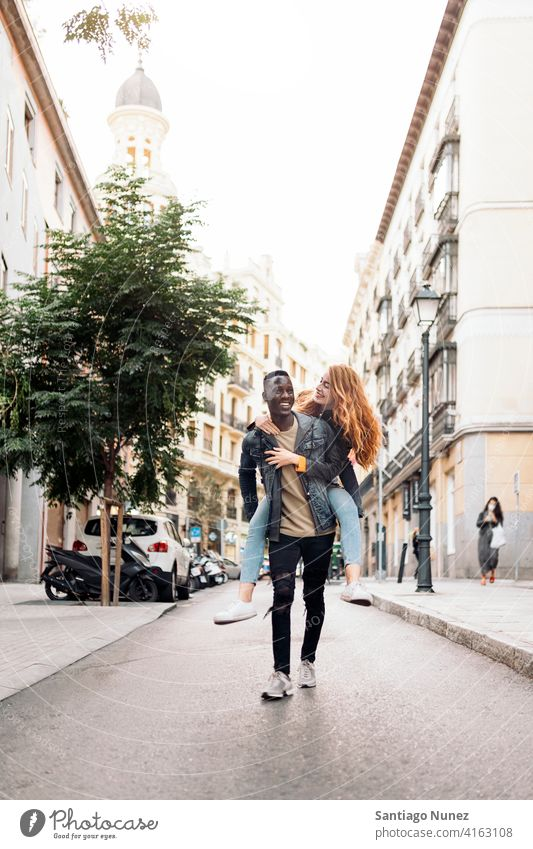 Schönes multiethnisches junges Paar laufen Spielen Spaß haben Straße Vorderansicht Porträt Partnerschaft multirassisch Schwarzer Mann Kaukasier multikulturell