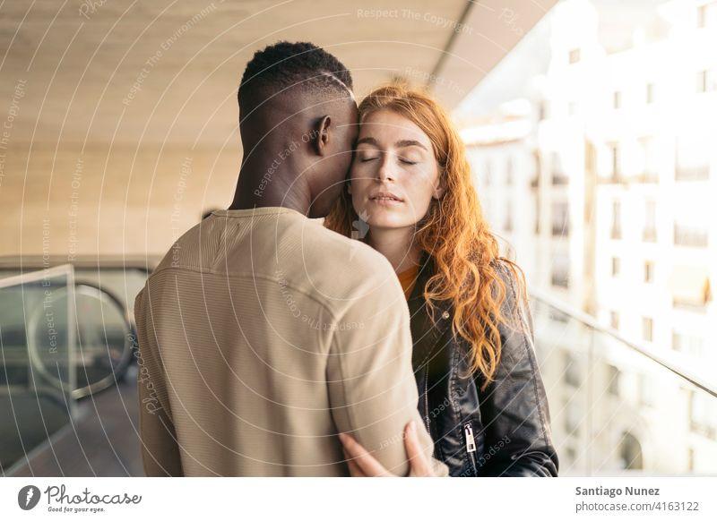 Liebendes multiethnisches Paar, das sich umarmt Augen geschlossen Porträt Vorderansicht umarmend Stehen Partnerschaft multirassisch Schwarzer Mann Kaukasier