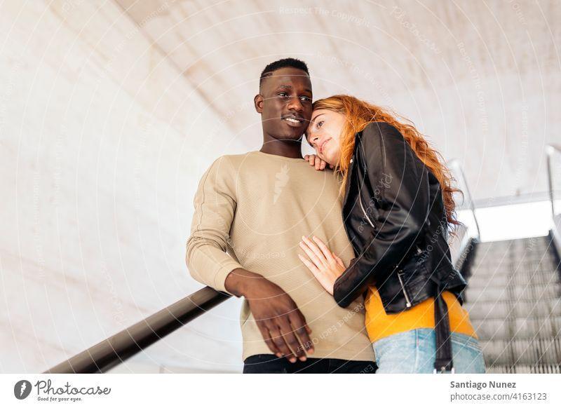 Liebevolles multiethnisches Paar-Portrait Treppe Lächeln umarmend die sich gegenseitig ansehen Porträt Vorderansicht Stehen Partnerschaft multirassisch