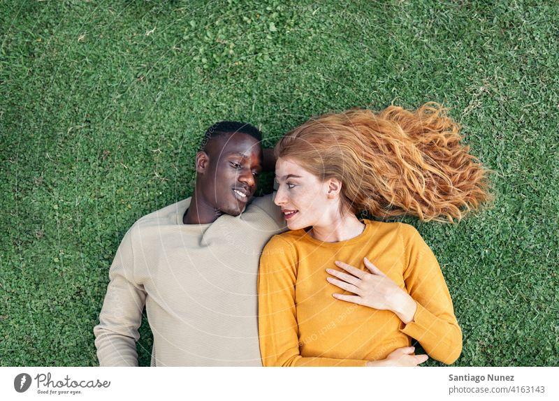 Multiethnische Paar Kuscheln im Gras Lügen die sich gegenseitig ansehen Draufsicht Porträt Partnerschaft multirassisch Schwarzer Mann Kaukasier multikulturell