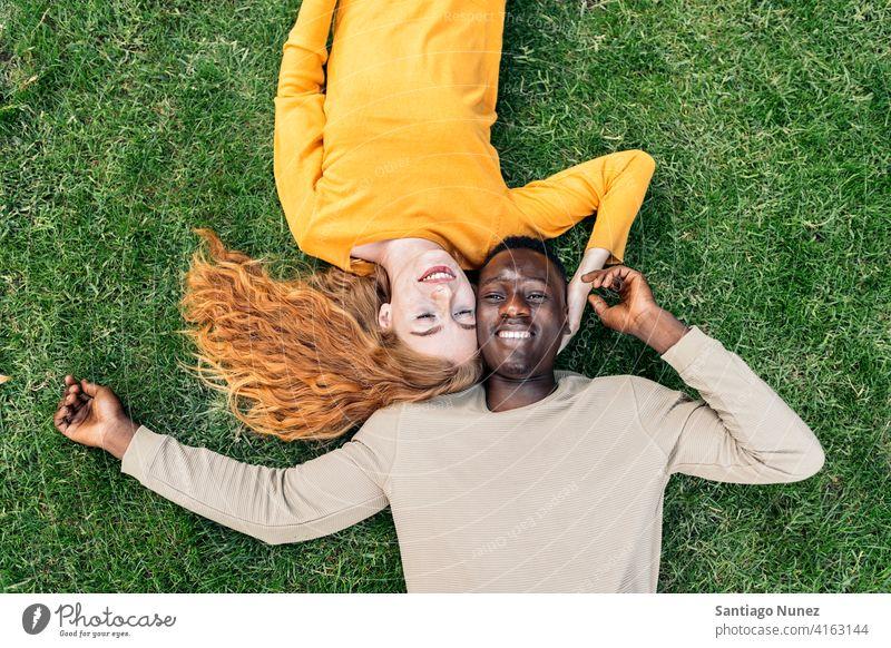 Multiethnische Paar Kuscheln im Gras Lügen Spaß haben Draufsicht Porträt Partnerschaft multirassisch Schwarzer Mann Kaukasier multikulturell multiethnisch