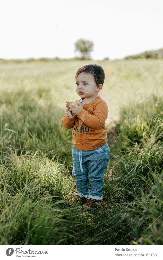 Kind isst Obst Junge 1-3 Jahre Kaukasier Essen Frucht Feld Frühling Tag Farbfoto Kindheit Kleinkind Mensch Außenaufnahme Spielen Leben mehrfarbig Freude Natur