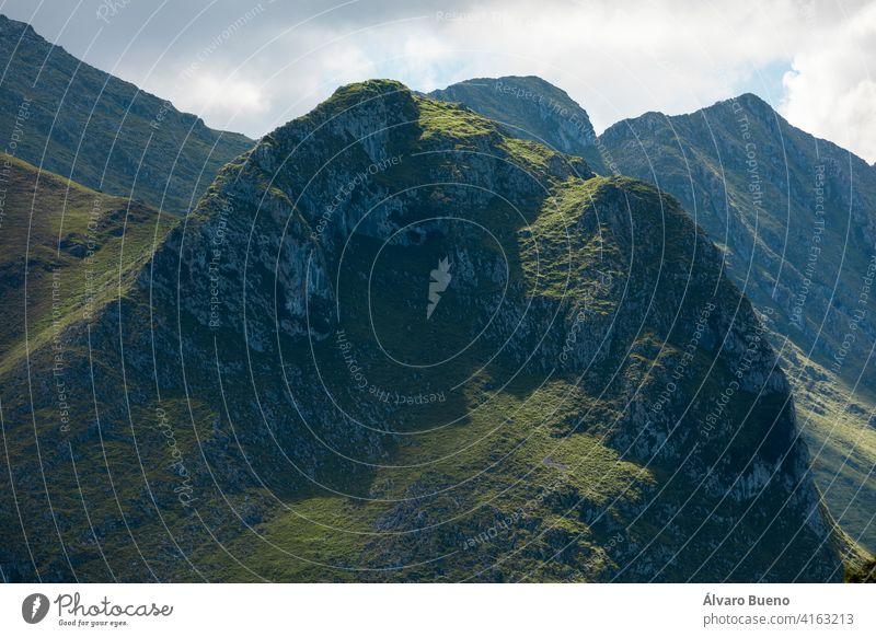 Riesige grüne Berge, schöne und erstaunliche ferne Gipfel, von der Sonne beleuchtet, im Nationalpark Picos de Europa, gesehen von Llanes, in der Nähe der Küste, in Asturien, Spanien.