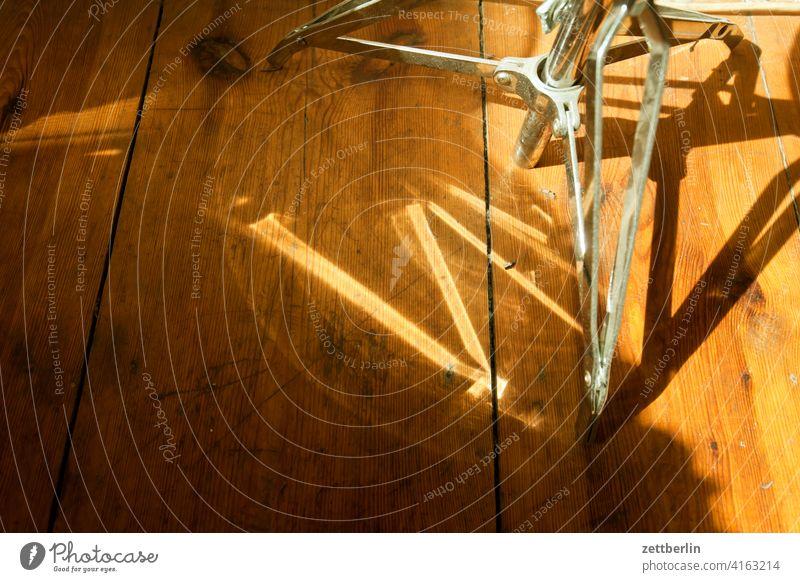 Schlagzeughocker mit Lichtreflexen stuhl metallhocker verstrebung streben sitz schlagzeughocker stuhl sitzgelegenheit holz boden diele stehen licht schatten