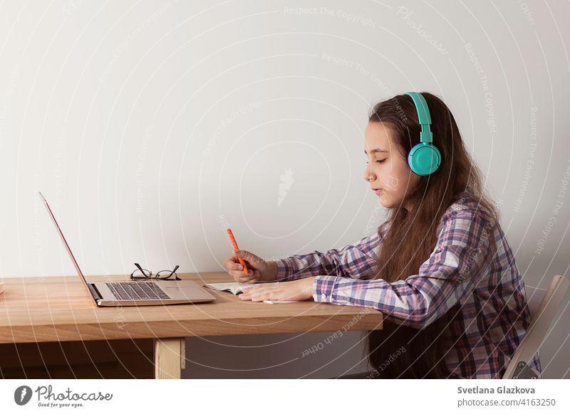Fernstudium zu Hause: Student mit Laptop, der mit Kopfhörern ein Webinar online anhört. Elearning-Konzept Entfernung Bildung Mädchen Frau Kind Kindheit Menschen