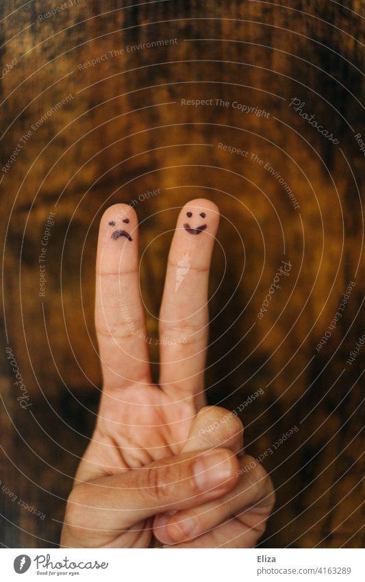 Ein trauriges und ein fröhliches Gesicht auf die Finger einer Hand gemalt. Emotionen. Traurig zwei verschieden Gefühle Freundschaft ungleich Partnerschaft