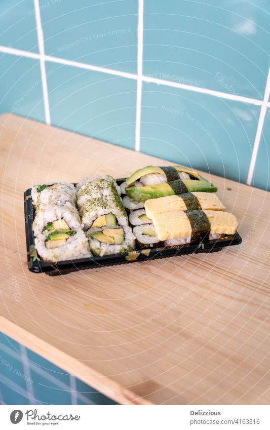 Frisches vegetarisches Sushi zum Mitnehmen auf hölzerner Oberfläche und blauem Kachelhintergrund Vegetarier Lebensmittel Hintergrund keine Menschen niemand