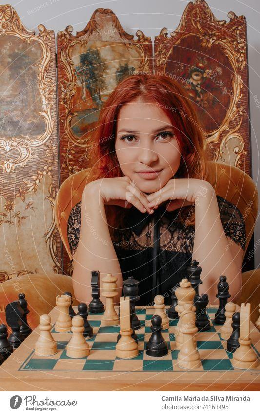 Schönes Mädchen spielen Schach, Königin Gambit spielen und jeder gewinnt, eine intelligente und nachdenklich Gesicht. Weiße und schwarze Schachfiguren sind auf dem Brett angezeigt. Mentales Spiel.