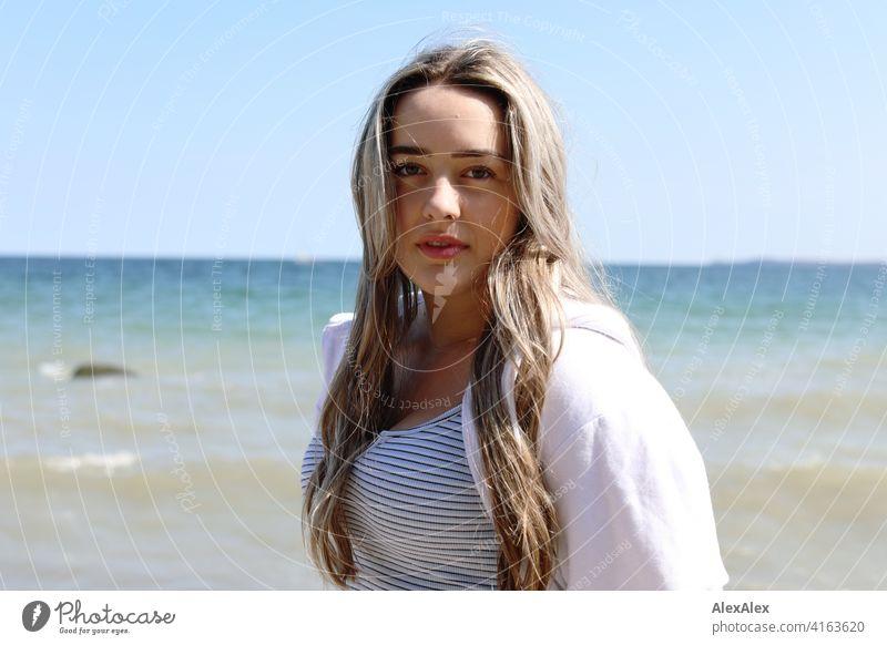 Ein schönes blondes Mädchen steht am Ostseestrand und schaut in die Kamera Lächeln freudig Landschaft von Freude Außenaufnahme Gesicht Junge Frau hübsch