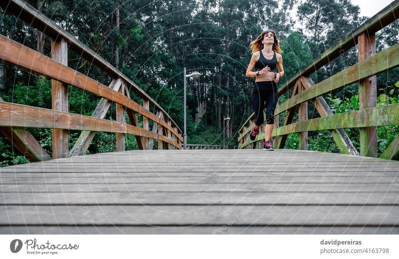 Frau rennt durch einen städtischen Park Sportlerin rennen müde anstrengen Holzsteg Ausdauer durchhalten Beständigkeit entschlossen Stadtpark Athlet heiter