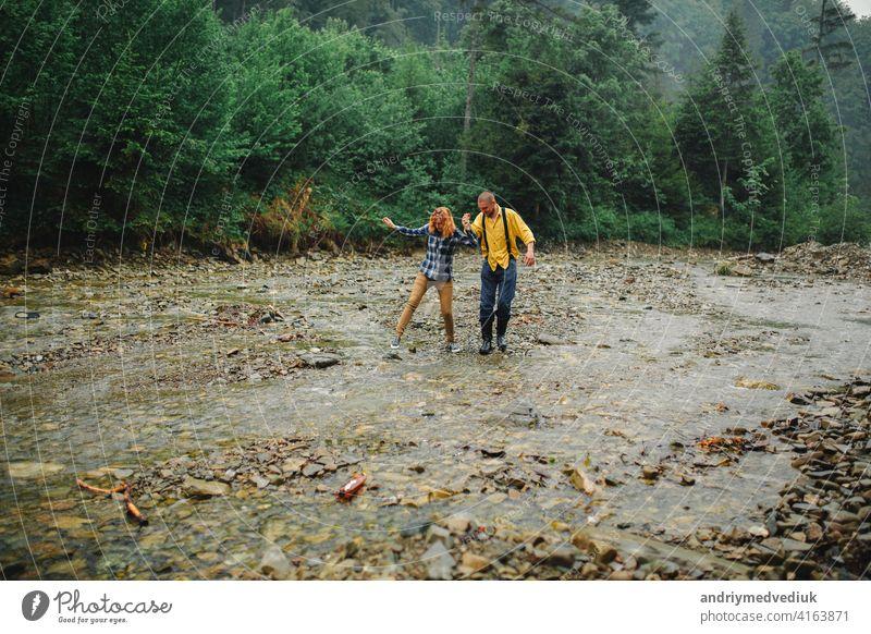 Playful glücklich gut aussehend Paar beim Spaziergang im Wald haben. Abenteuer in der Natur Konzept. Paar in den Bergen Glück aktiv Partnerschaft Wälder Liebe