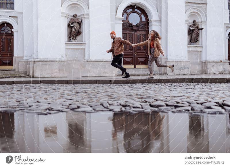 Glückliche junge stilvolle Paar, genießen ihren Spaziergang in alten Straße in der Stadt Straße mit alten Gebäude auf dem Hintergrund nach regen. selektiven Fokus.