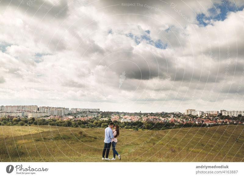 junge Paar hat Spaß auf ihren Sommerurlaub. stilvolle Mann und Frau springen, laufen und genießen Sommertag außerhalb der Stadt Feiertag Freund Gras Feld habend
