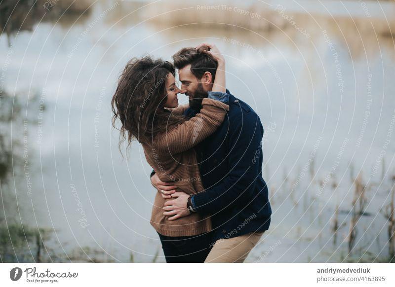 Zwei kaukasische Liebhaber in der Nähe des Sees. Junges Paar umarmt sich am Herbsttag im Freien. Ein bärtiger Mann und lockige Frau in der Liebe. Valentinstag. Konzept der Liebe