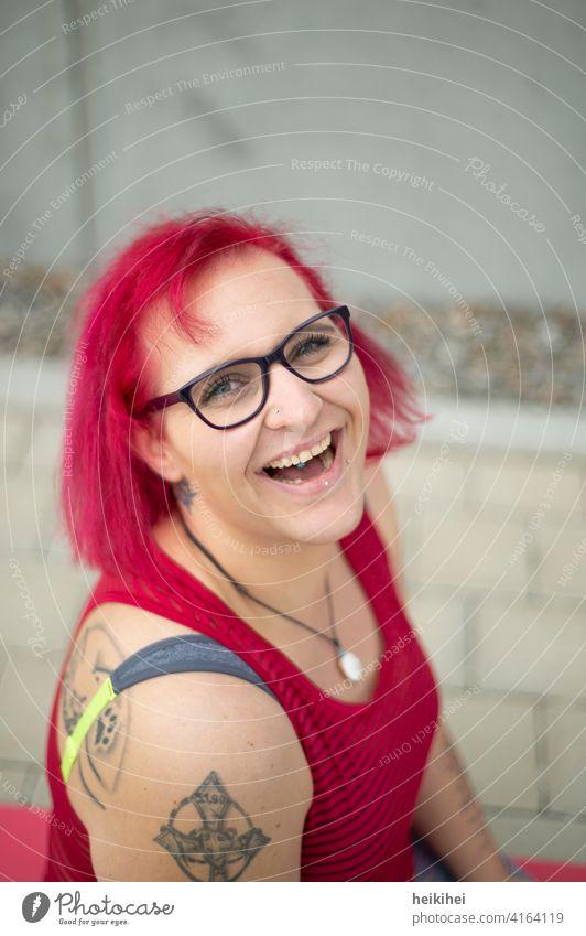 Eine junge rothaarige Frau mit Brille und Tattoos schaut lachend in die Kamera frau brille tattoos portrait lippenpiercing auffallend erscheinungsbild