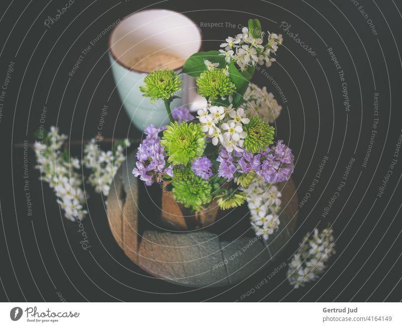 Stillleben mit Blumen und Kaffeetasse auf dunklem Hintergrund Frühling Farbfoto Pflanze Blüte Natur Nahaufnahme grün Menschenleer innen