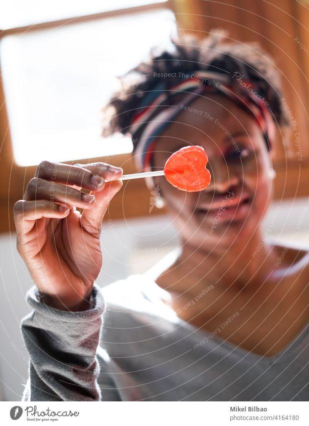 Junge schwarze Frau zu Hause lächelnd mit einem Lutscher in der Hand Schönheit Afroamerikaner Afrikanisch Menschen Dame Model Ausdruck Frisur im Innenbereich