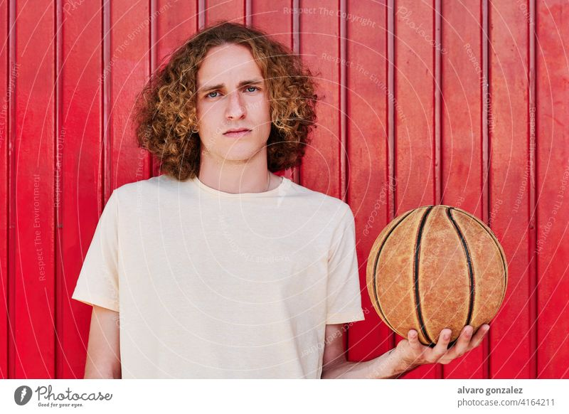 ein junger Mann mit lockigem Haar und grünen Augen, der mit einem Basketball in der Hand in die Kamera schaut che Ball Person Korb Sport sportlich männlich