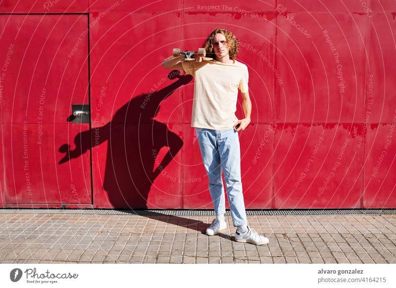 ein junger Mann mit lockigem Haar und seinem Skateboard mit rotem Hintergrund an einem sonnigen Sommertag Basketball Ball Person Korb Sport sportlich männlich
