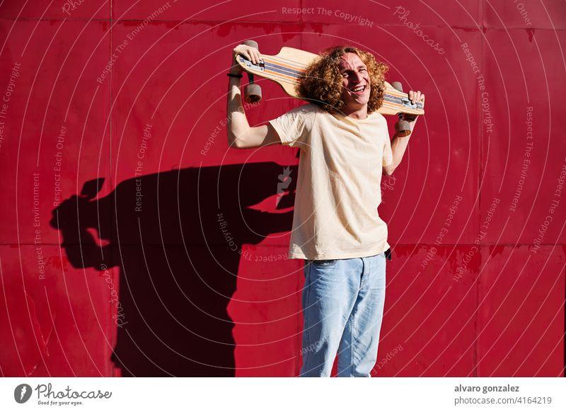 junger Mann mit lockigem Haar, der in die Kamera schaut, mit seinem Skateboard auf den Schultern und einem roten Hintergrund Longboard che attraktiv Person