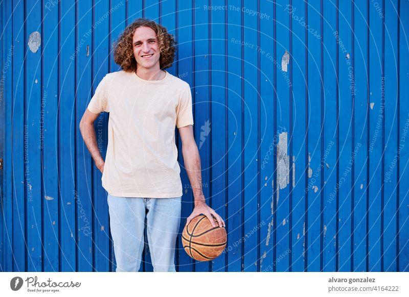 junger Mann mit lockigem Haar mit seinem Basketball in der Hand che Ball Person Korb Sport sportlich männlich Spiel Spieler wettbewerbsfähig Hintergrund
